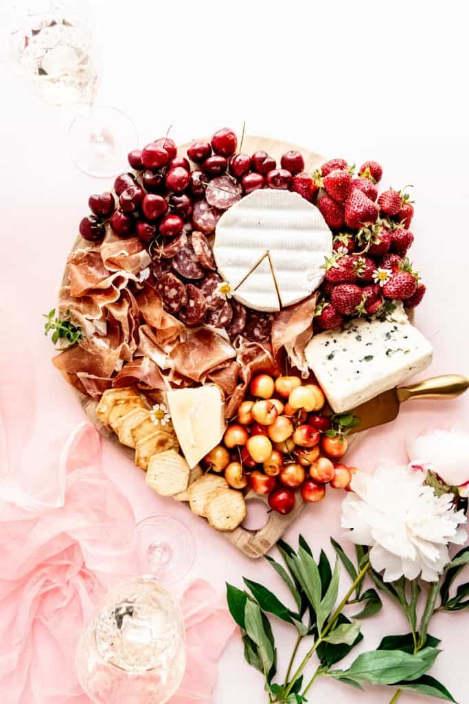 overhead shot of summer charcuterie board with wine glasses and peonies