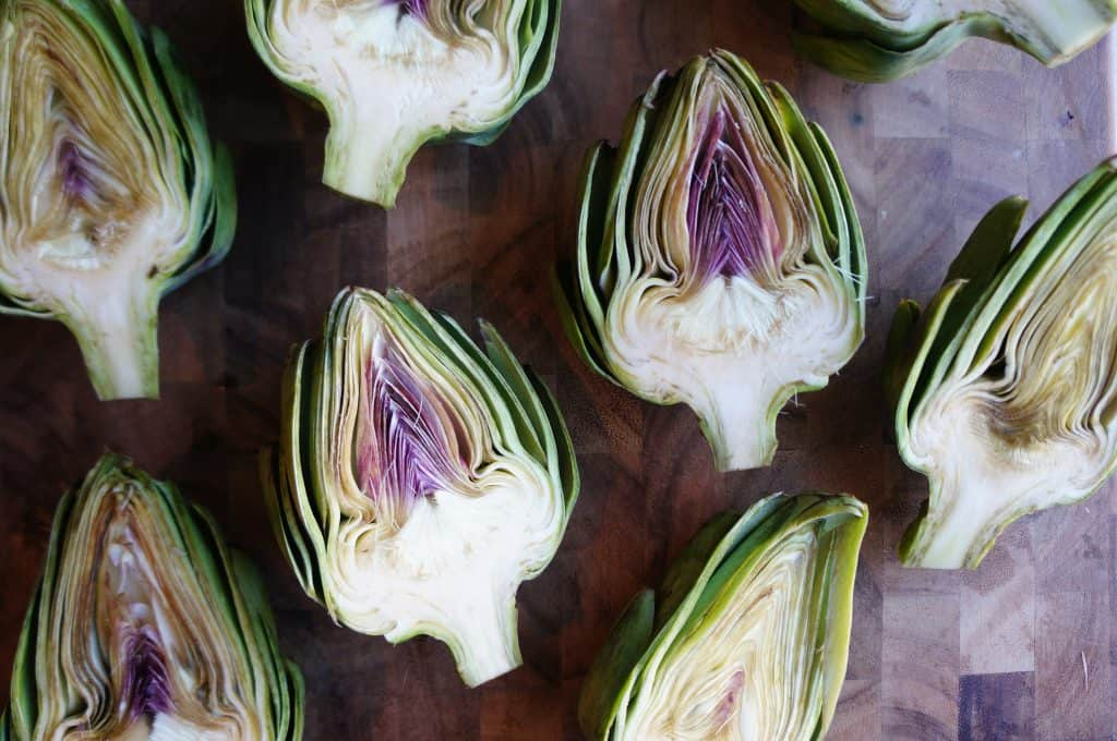 raw artichokes sliced in half cut side up on cutting board