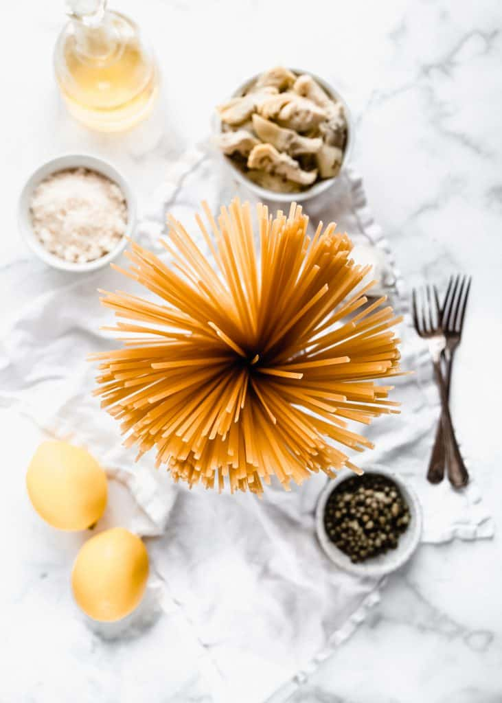 top view of linguine pasta, lemons, capers, parmesan and artichoke hearts on marble background
