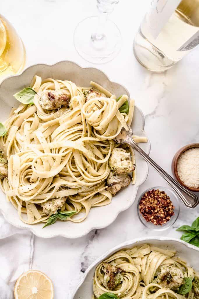 chicken pesto pasta in scalloped bowl withpasta twirled around fork