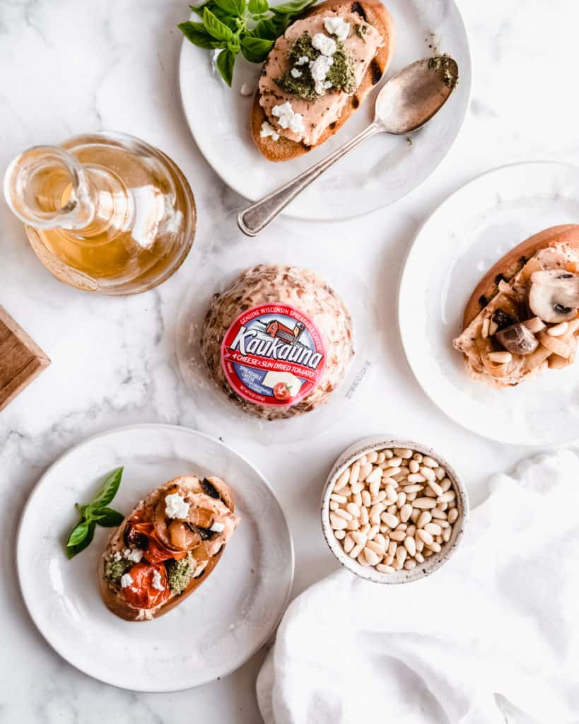 Three plates with assembled bruschetta with various toppings on plates, kaukauna cheese ball in the middle and a bottle of olive oil all on the marble background