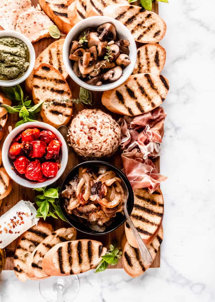 close up of caramelized onions, prosciutto, sauteed mushrooms, and roasted grape tomatoes on board in bowls with grilled bread surrounding