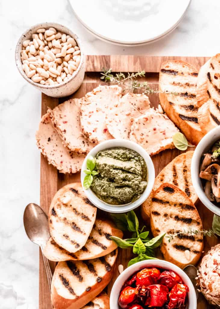 close up of pesto, on board in bowls with grilled bread surrounding