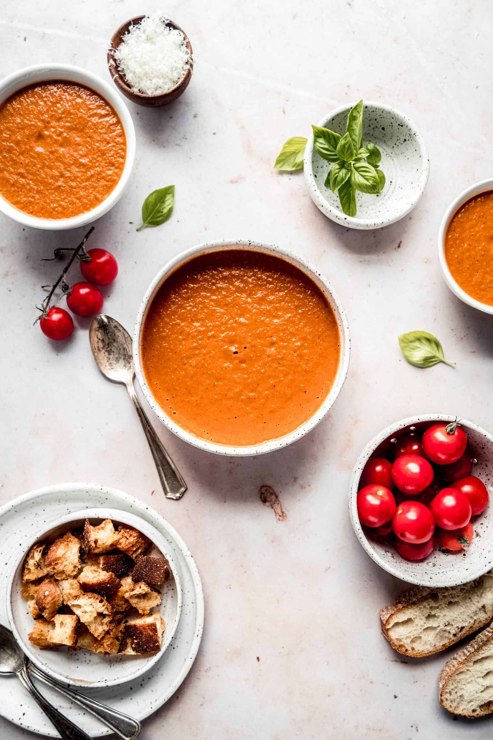 Roasted tomato soup in bowls with smaller bowls of fresh basil, parmesan cheese, cherry tomatoes and croutons