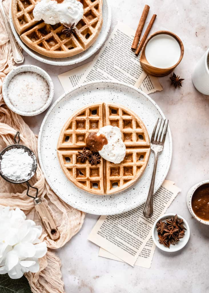 apple butter waffles garnished with cinnamon whipped cream and apple butter on plate next to cup of coffee and maple syrup in wood cup