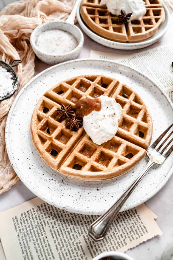 close up shot of apple butter waffles garnished with cinnamon whipped cream and apple butter on plate