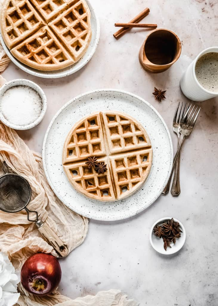 apple butter waffles on plate next to cup of coffee and maple syrup in wood cup